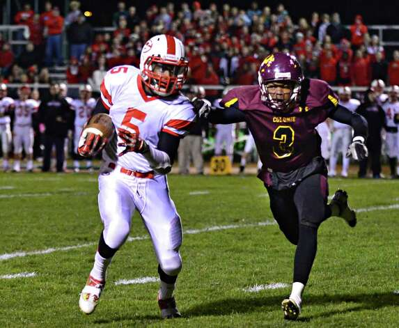 Guilderland's #5 Micaiah Henningham, left, gets away from Colonie defender Gaddy Khyan to score  during the Class AA quarterfinal football game Friday Oct. 24, 2013, in Colonie, NY.  (John Carl D'Annibale / Times Union) Photo: John Carl D'Annibale / 00024382A