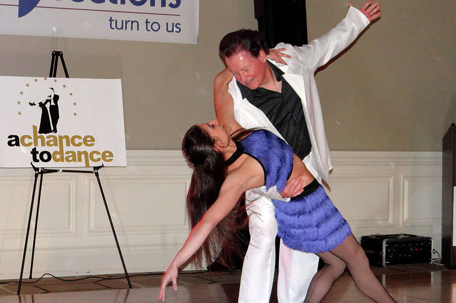"Channeling John Travolta from ""Saturday Night Fever,"" First Selectman Michael Tetreau -- sporting a white disco suit and dark-dyed hair -- hit the dance floor with Tiffany Petrocelli at Friday's ""A Chance to Dance"" benefiting Positive Directions at the Patterson Club in Fairfield. Photo: Mike Lauterborn / Fairfield Citizen contributed"