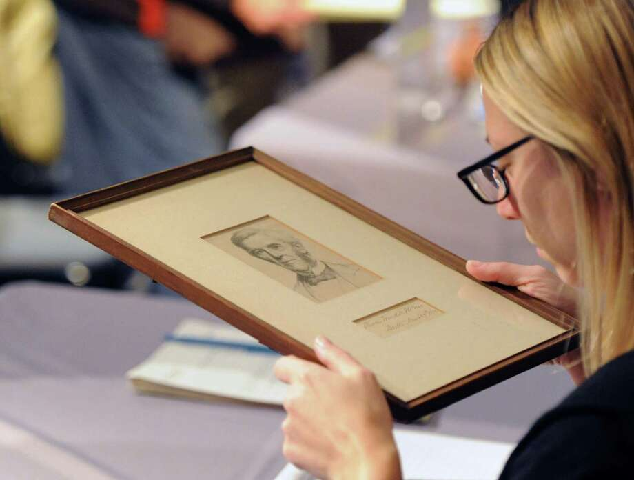 Cassandra Hatton of Bonhams Auctioneers & Appraisers, inspects a drawing during Appraisal Day at the Bruce Museum in Greenwich, Saturday, Oct. 26, 2013. Specialists from Bonhams, the British auction house, came to the Bruce to give appraisals to the public. Photo: Bob Luckey / Greenwich Time
