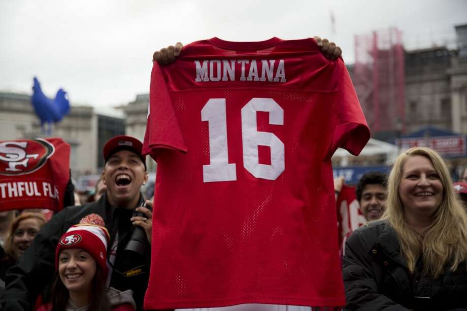 A San Francisco 49ers fan holds up a shirt bearing the name of their former quarterback Joe Montana during an NFL fan rally in Trafalgar Square, London, Saturday, Oct. 26, 2013.  The San Francisco 49ers are due to play the the Jacksonville Jaguars at Wembley stadium in London on Sunday, Oct. 27 in a regular season NFL game.  (AP Photo/Matt Dunham) Photo: Matt Dunham, Associated Press