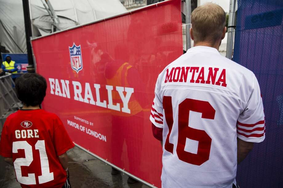 A San Francisco 49ers fan wearing a shirt bearing the name of their former quarterback Joe Montana looks into a backstage area during an NFL fan rally in Trafalgar Square, London, Saturday, Oct. 26, 2013. The San Francisco 49ers are due to play the the Jacksonville Jaguars at Wembley stadium in London on Sunday, Oct. 27 in a regular season NFL game. (AP Photo/Matt Dunham) Photo: Matt Dunham, Associated Press