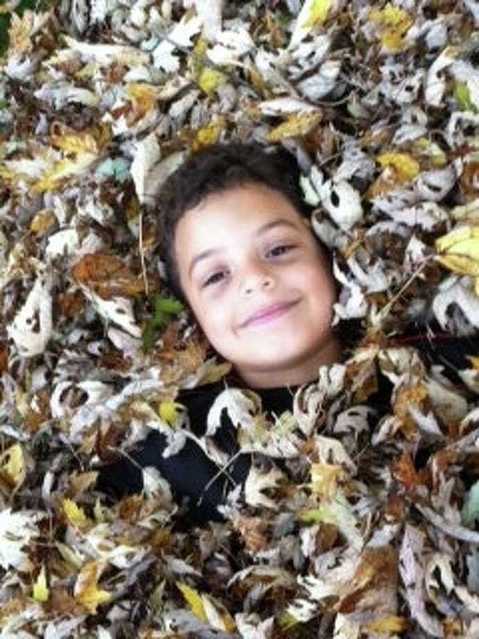 "After a hard five minutes of helping his mom. Jennifer Chatain. gather leaves, Elijah decided to make leaf angels and bury himself. Elijah, 6, attends Saint Kateri Parish School and was excited to play in the leaves because the Colonie family's old home was on a busy street with no yard or leaves. ""That is probably why he tried to make snow angels in leaves! Of course, when he stood up and looked for the angel he looked at me and said, 'Oh well, it looks like a hammer!'""Chatain says."