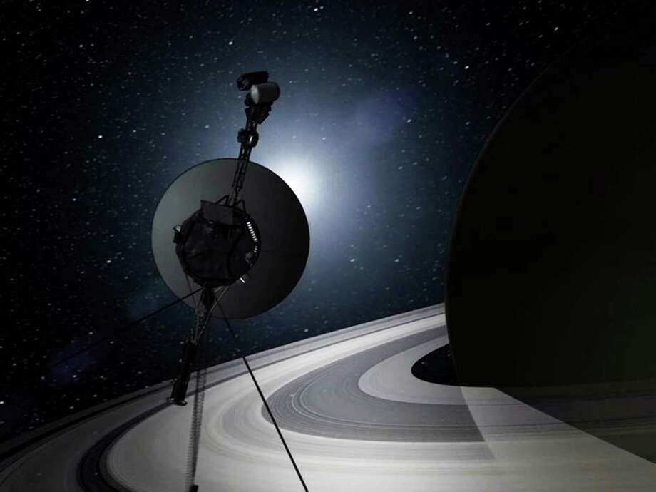 This artist's rendering provided by NASA shows Voyager 1 traversing Saturn's rings. Thirty-six years after leaving Earth, the probe entered interstellar space. Photo: HOPD / NASA
