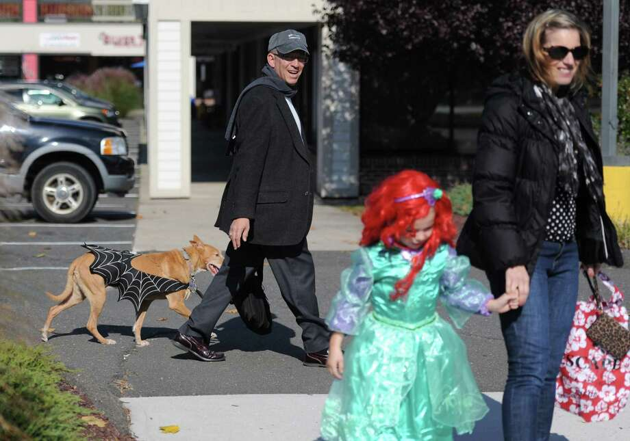 Bethel Green Party First Selectman candidate Al Vargas walks his dog, a Pondango named Dear, dressed as Batdog, as Sharon Sherry, of Danbury, and her 6-year old daughter Kaitlyn, dressed as Ariel, walk down Greenwood Avenue for the Bethel Trick or Treat Halloween Street Bash in downtown Bethel, Conn. on Saturday, Oct. 26, 2013.  Hundreds of kids and parents walked through the streets dressed as zombies, princesses, animals and more, going from door-to-door at participating businesses.  The municipal center lawn also featured many fun games and activities for children. Photo: Tyler Sizemore / The News-Times