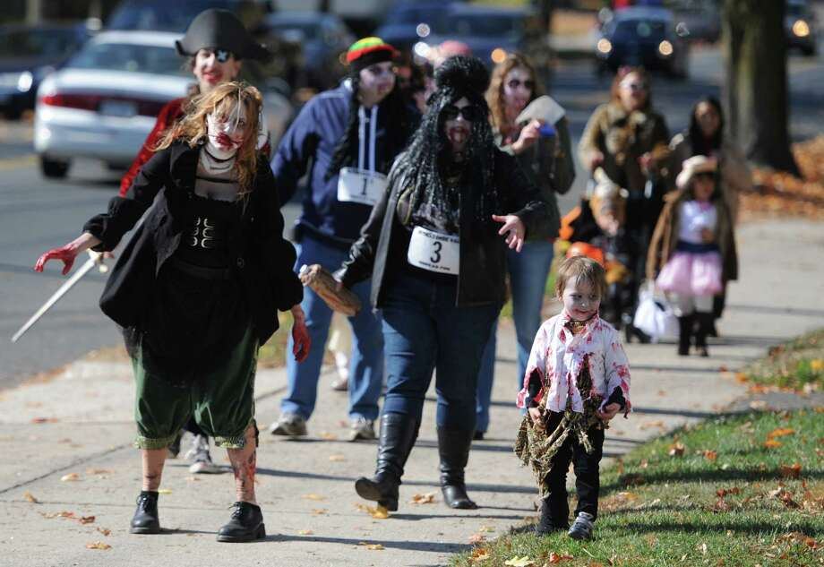 A pack of zombies stroll down Greenwood Avenue for the Bethel Trick or Treat Halloween Street Bash in downtown Bethel, Conn. on Saturday, Oct. 26, 2013.  Hundreds of kids and parents walked through the streets dressed as zombies, princesses, animals and more, going from door-to-door at participating businesses.  The municipal center lawn also featured many fun games and activities for children. Photo: Tyler Sizemore / The News-Times