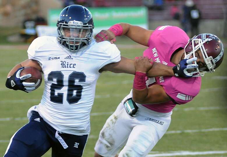 Rice running back Turner Petersen stiff arms New Mexico State University's Davis Cazares.