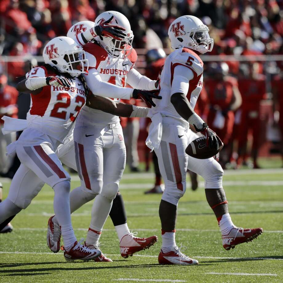 UH players congratulate Turon Walker on his interception against Rutgers. Photo: Mel Evans, Associated Press