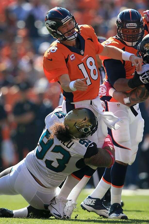 Jacksonville's Tyson Alualu hits Peyton Manning as the Broncos' QB passes. Photo: Doug Pensinger, Getty Images