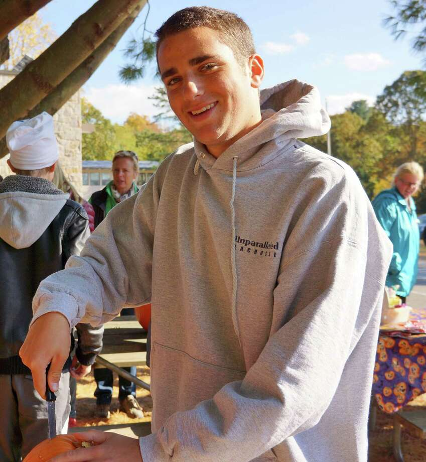 Ethan Kobak, a Staples High School junior, was on hand to help with the pumpkin carving Saturday at Earthplace. Photo: Todd Tracy / Westport News contributed