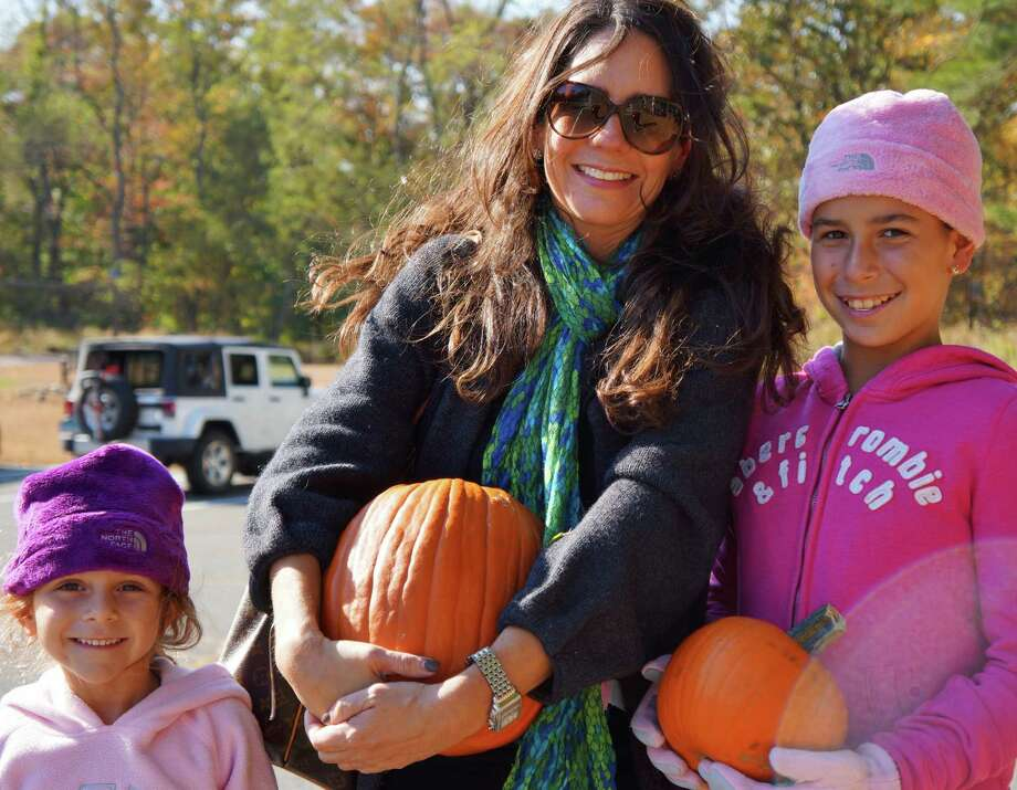 Maria Devito of Greenwich with daughters Olivia on left and Allissandra at the pumpkin-carving event Saturday at Earthplace. Photo: Todd Tracy / Westport News contributed
