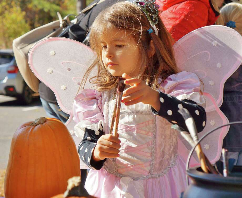 Miranda Falk, 4, of Westport, had a magical  moment Saturday as she considered carving a pumpkin for Halloween at Earthplace on Saturday. Photo: Todd Tracy / Westport News contributed