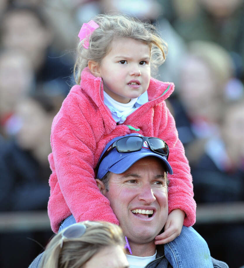 Kolbie Douglas, 4, rides high on the shoulders of her dad, Keith Douglass, while watching the Greenwich High School Homecoming activities during halftime of the football game between Greenwich and Fairfield Warde High School at Greenwich, Saturday, Oct. 26, 2013. Photo: Bob Luckey / Greenwich Time
