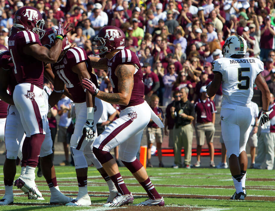 Teammates celebrate with Texas A&M Aggies wide receiver Derel Walker after he caught a touchdown pass while Vanderbilt Commodores defensive back Torren McGaster makes his way off the field during the first half of a college football game at Kyle Field Saturday, Oct. 26, 2013, in College Station. Photo: Cody Duty, Houston Chronicle / © 2013 Houston Chronicle