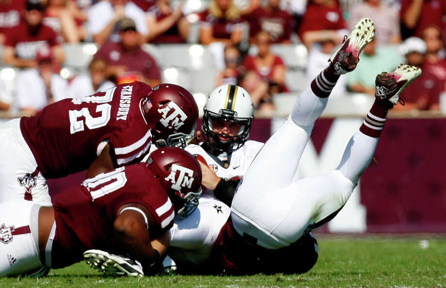 A host of Texas A&M Aggies wrap up Vanderbilt Commodores quarterback Patton Robinette during the first half of a college football game at Kyle Field Saturday, Oct. 26, 2013, in College Station. Photo: Cody Duty, Houston Chronicle / © 2013 Houston Chronicle
