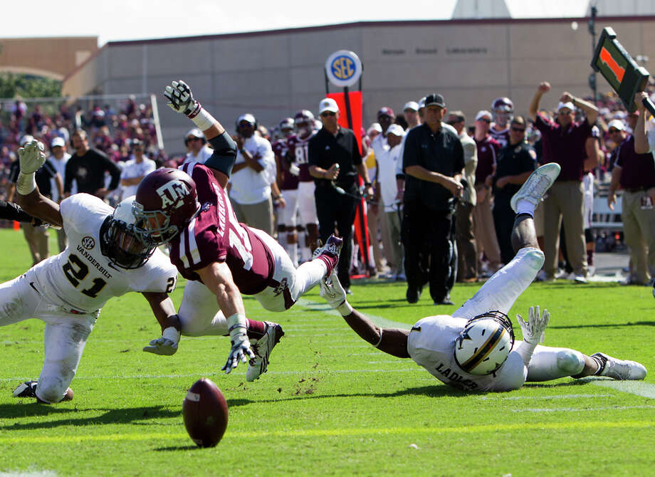 Vanderbilt Commodores defensive back Paris Head, left, and safety Kenny Ladler, right, force a fumble from Texas A&M Aggies wide receiver Travis Labhart, center, during the second half of a college football game at Kyle Field Saturday, Oct. 26, 2013, in College Station. Photo: Cody Duty, Houston Chronicle / © 2013 Houston Chronicle