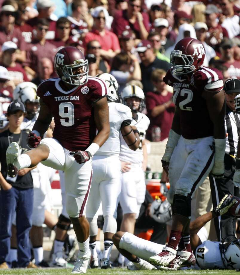 Texas A&M Aggies linebacker Nate Askew, left, celebrates an interception intended for Vanderbilt Commodores wide receiver Jordan Matthews during the third quarter of a college football game at Kyle Field Saturday, Oct. 26, 2013, in College Station. The Aggies won 56-24. Photo: Cody Duty, Houston Chronicle