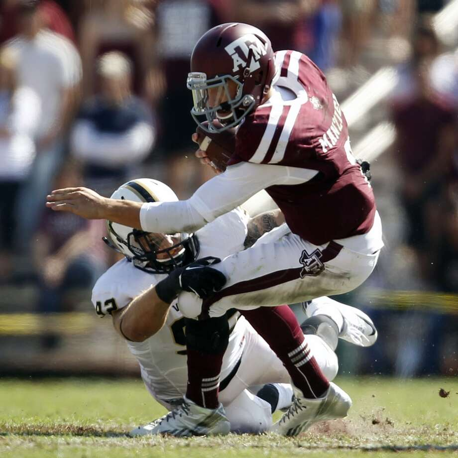 Texas A&M's Johnny Manziel, right, is sacked by Vanderbilt's Kyle Woestmann during the first half of an NCAA college football game, Saturday, Oct. 26, 2013, in College Station, Texas. Photo: Eric Christian Smith, Associated Press