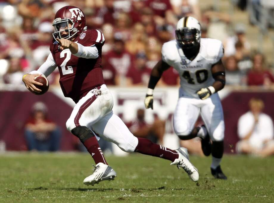 Texas A&M's Johnny Manziel (2) runs past Vanderbilt's Ja'karri Thomas (40) during the first half of an NCAA football game, Saturday, Oct. 26, 2013, in College Station, Texas. Photo: Eric Christian Smith, Associated Press
