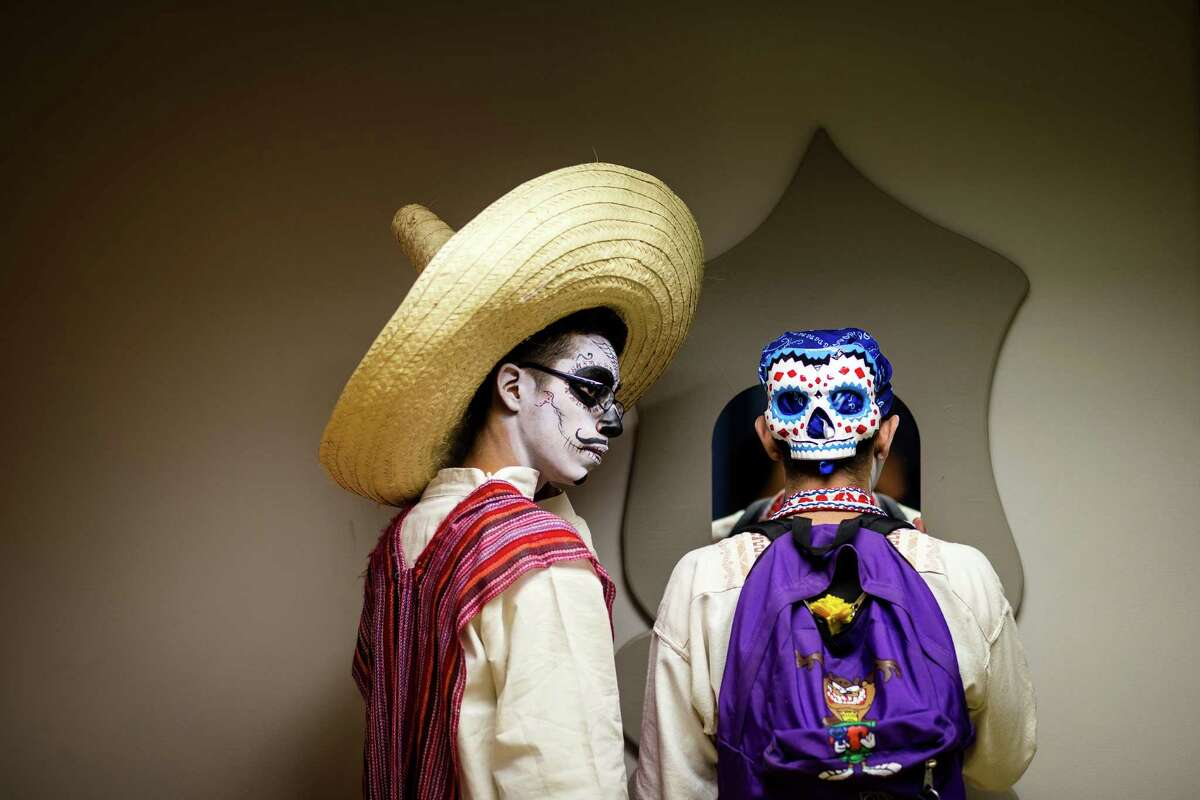 Young men in traditional sugar skull makeup check out their faces in a mirror during the Dia De Los Muertos