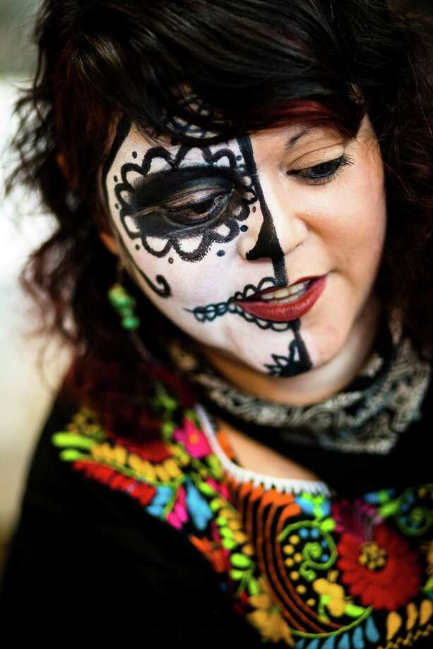 "A makeup artist decked out in sugar skull facepaint applies the look to children during the Dia De Los Muertos ""A Mexican Celebration to Remember Our Departed"" event Saturday, Oct. 26, 2013, in The Armory in the Seattle Center in Seattle. The festival honors the lives of loved ones who have passed with homage from community altars, sugar skulls, special food, candles, music and dance. The event continues Sunday. Photo: JORDAN STEAD, SEATTLEPI.COM / SEATTLEPI.COM"
