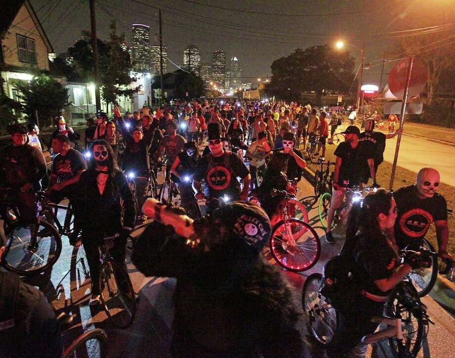 Thousands of bicyclists - many in Halloween costumes - wait for a train Friday night at a railroad crossing on Houston Avenue during the Critical Mass bike ride in Houston. Photo: James Nielsen, Staff / © 2013  Houston Chronicle