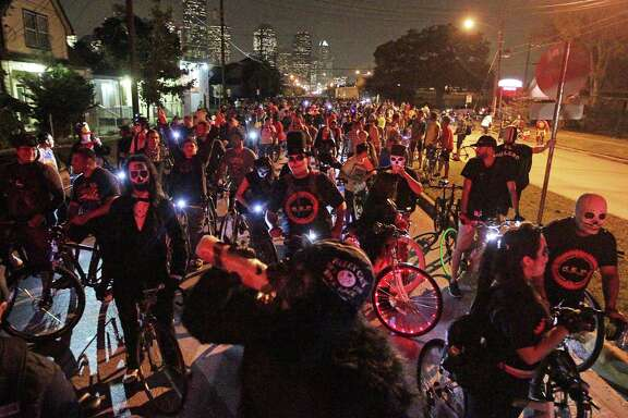 Thousands of bicyclists - many in Halloween costumes - wait for a train Friday night at a railroad crossing on Houston Avenue during the Critical Mass bike ride in Houston.