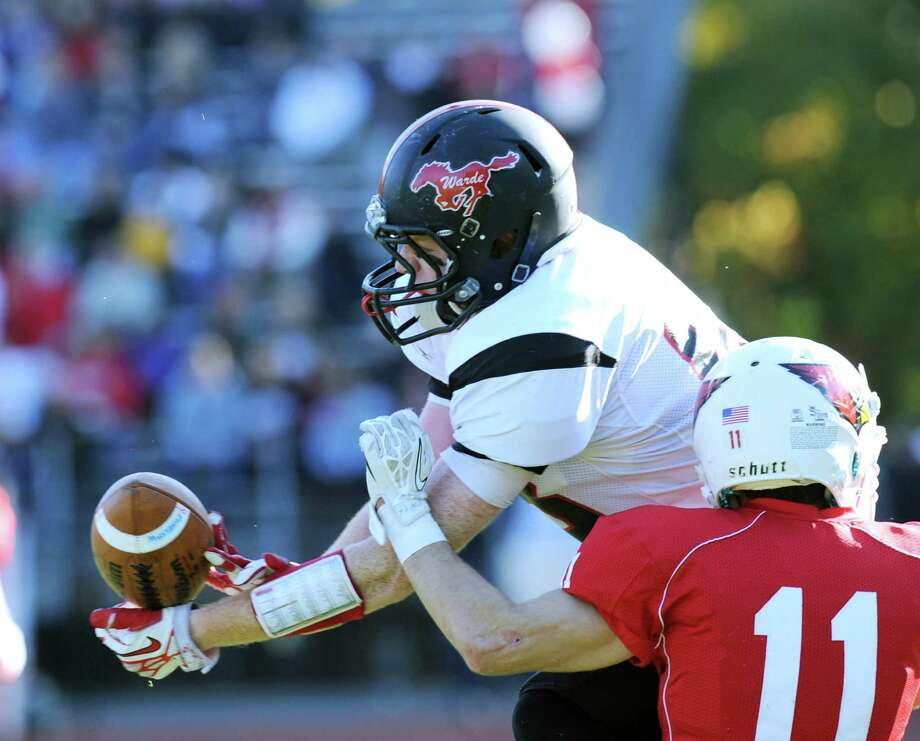 At right, Ryan Pasquali (# 11) of Greenwich, breaks up a pass play to a Fairfield Warde receiver during the High school football game between Greenwich High School and Fairfield Warde High School at Greenwich, Saturday, Oct. 26, 2013. Greenwich defeated Warde, 42-7. Photo: Bob Luckey / Greenwich Time