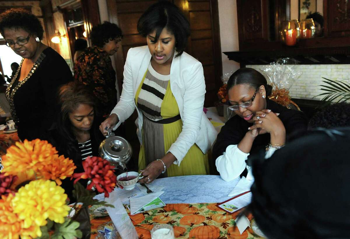 Association treasurer Michelle Hewitt, center, pours tea for guests Elisha Cleary, left, and Jaleesce Brown, both of Albany, during Tea 4 Two on Saturday, Oct. 26, 2013, at the Women's Club of Albany in Albany, N.Y. At top left is Carolyn McLaughlin, president of the Common Council. The Black Womena€™s Association of Albany hosted the 2nd annual event to benefit the BWAA Marian I. Hughes Scholarship Fund. The college scholarships are awarded to qualifying minority girls who are high school seniors in the Capital Region. (Cindy Schultz / Times Union)
