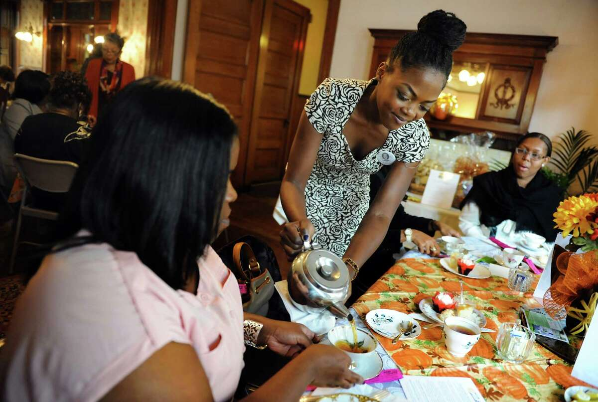Denee Easy, center, pours tea for fellow association member Latelle Norville, left, during Tea 4 Two on Saturday, Oct. 26, 2013, at the Women's Club of Albany in Albany, N.Y. The Black Womena€™s Association of Albany hosted the 2nd annual event to benefit the BWAA Marian I. Hughes Scholarship Fund. The college scholarships are awarded to qualifying minority girls who are high school seniors in the Capital Region. (Cindy Schultz / Times Union)