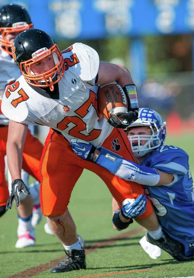 Darien high school's John Reed tackles Ridgefield high school's running back James Turner during a football game played at Darien high school, Darien, CT on Saturday, October, 26th, 2013 Photo: Mark Conrad / Stamford Advocate Freelance