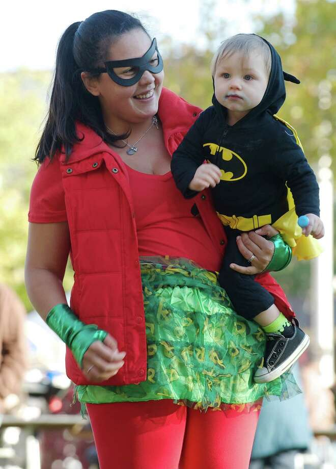 Teresa Wolfe, of Bethel, gives her son Maxwell Wolfe, 1 1/2 a lift while he enjoys his first ever lollipop at the 21st annual Halloween on the Green in Danbury, Conn, on Saturday October 26, 2013. They are dressed as Batman and Robin. Photo: H John Voorhees III / The News-Times Freelance