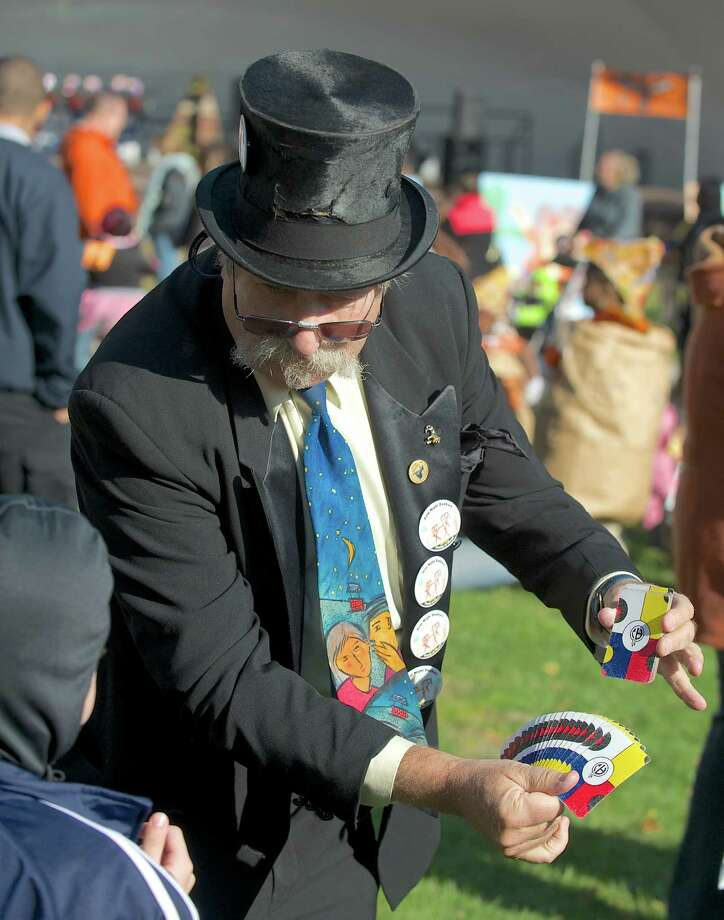 """Magic Marty"" Marty Steinberg, a volunteer with the Lion's Club, entertains a child with a card trick during the 21st annual Halloween on the Green in Danbury, Conn, on Saturday October 26, 2013. Photo: H John Voorhees III / The News-Times Freelance"