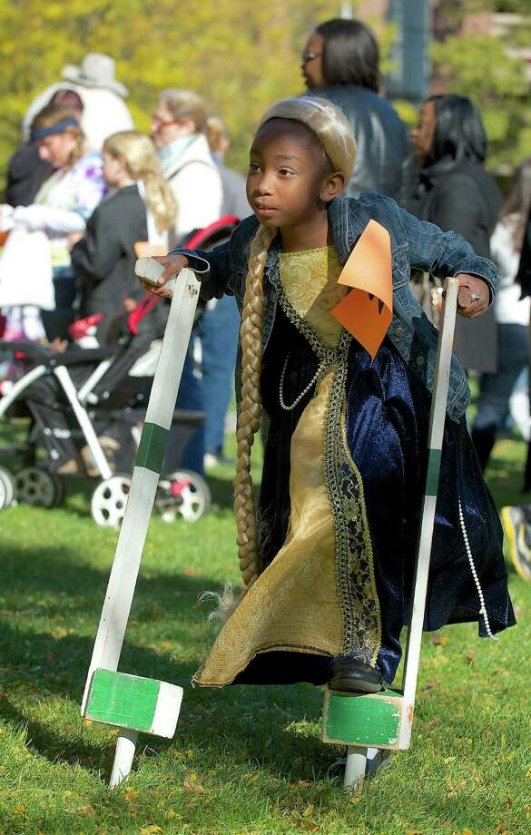 Maya Chiappetta, 7, of Danbury tries a pair of stilts at the 21st annual Halloween on the Green in Danbury, Conn, on Saturday October 26, 2013. Chippetta is dressed as Rapunzel. Photo: H John Voorhees III / The News-Times Freelance