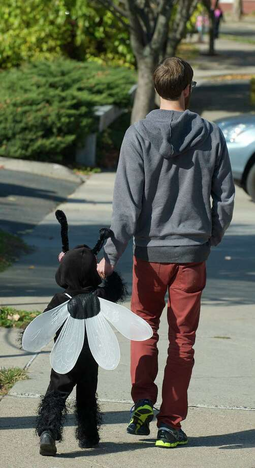 Nico Larosa, 2 1/2, of Danbury, walks to the 21st annual Halloween on the Green in Danbury, Conn, with his dad John Larosa on Saturday October 26, 2013. Nico is dressed as a Little Fly. Photo: H John Voorhees III / The News-Times Freelance
