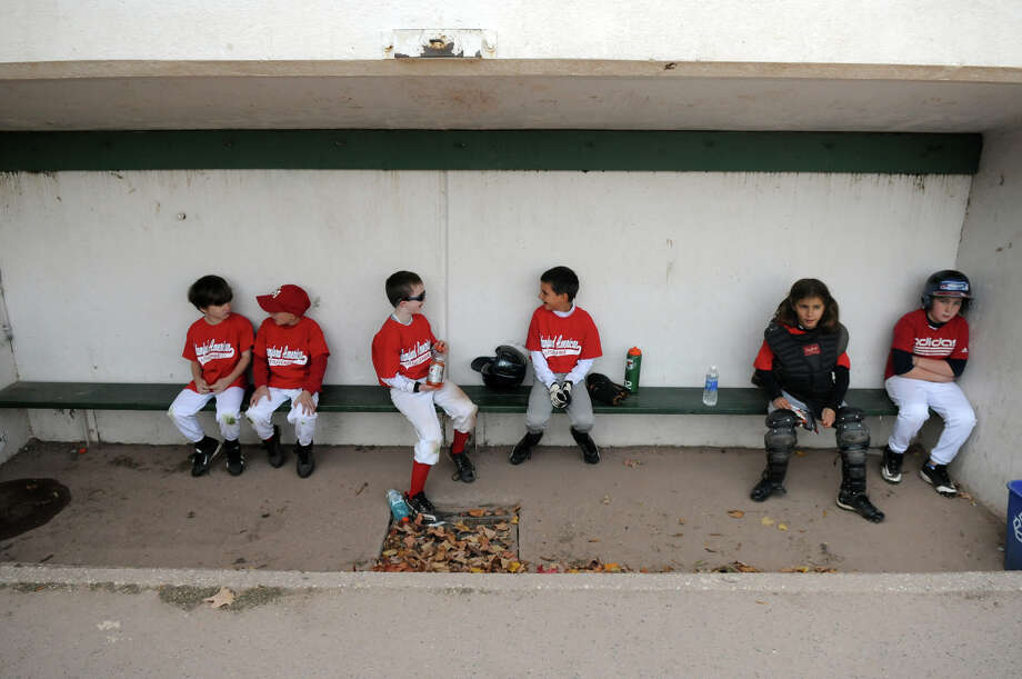 The Stamford American Little League players take a break in the dugout as they play what might be its last game at Springdale School in Stamford, Conn., Oct. 26, 2013. The team is hoping the Parks and Recreation Board intervenes in a dispute with the league's board over a merger with the North Stamford Little League. Photo: Keelin Daly / Stamford Advocate Freelance