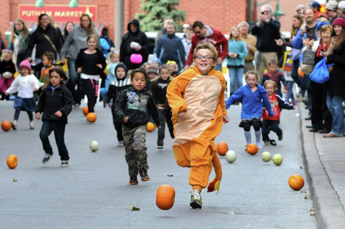 Wearing his Pokeman costume, Aidan Cole, 8, of Wilton, center, leads in a pumpkin roll down Caroline Street during the Saratoga Springs Fall Festival on Saturday, Oct. 26, 2013, in Saratoga Springs, N.Y. The event featured family entertainment, face painting, games and a costume parade. (Cindy Schultz / Times Union)