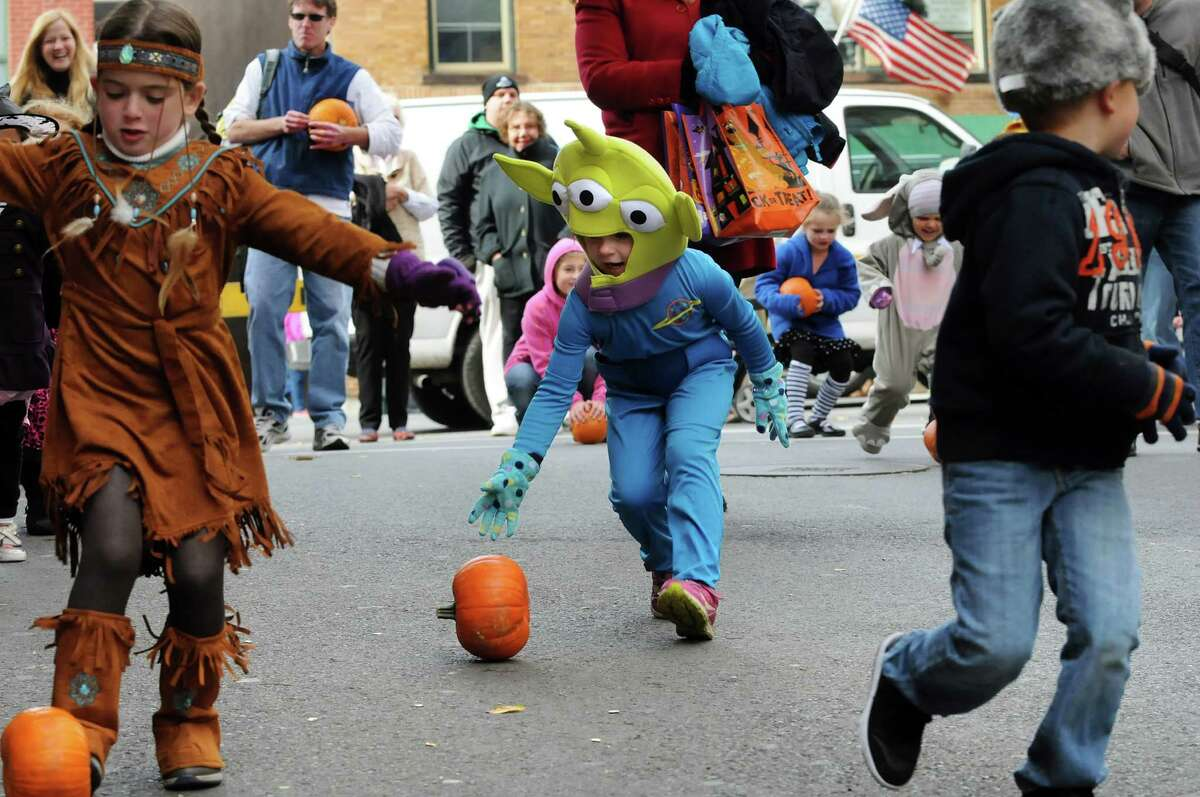 Wearing an alien costume, Aidia Hunter, 5, of Ballston Spa, center, takes part in a pumpkin roll down Caroline Street during the Saratoga Springs Fall Festival on Saturday, Oct. 26, 2013, in Saratoga Springs, N.Y. The event featured family entertainment, face painting, games and a costume parade. (Cindy Schultz / Times Union)