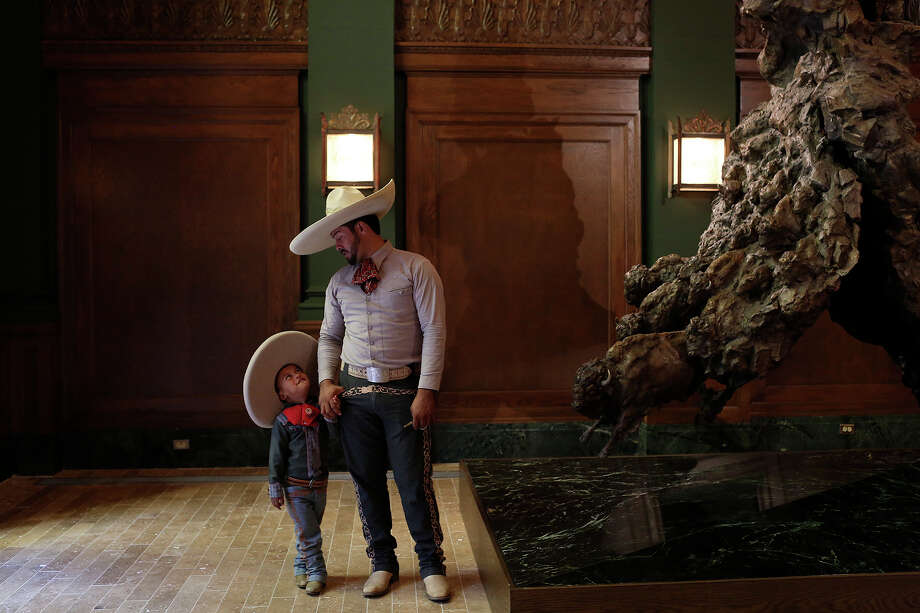 Carlos Franco and his son, Carlos Franco, Jr., 3, stand next to John Coleman's Visions of Change at the Briscoe Western Art Museum after performing during the grand opening celebration for the museum in San Antonio on Saturday, Oct. 26, 2013. Photo: Lisa Krantz, San Antonio Express-News / San Antonio Express-News