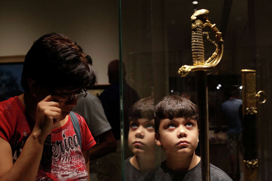 Teresa Lesczynski and her son, Ian Lesczynski, 9, view Santa Anna's sword during the grand opening celebration for the Briscoe Western Art Museum in San Antonio on Saturday, Oct. 26, 2013. Photo: Lisa Krantz, San Antonio Express-News / San Antonio Express-News