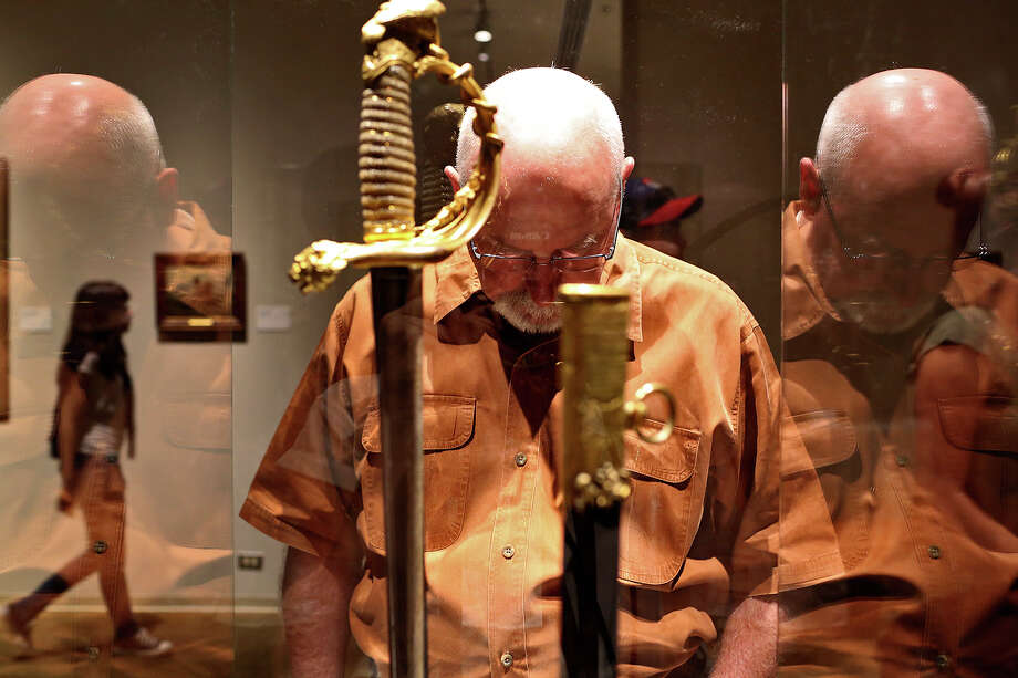 Rick Swinghamer, of Boerne, reads about Santa Anna's Sword on display during the grand opening celebration for the Briscoe Western Art Museum in San Antonio on Saturday, Oct. 26, 2013. Photo: Lisa Krantz, San Antonio Express-News / San Antonio Express-News