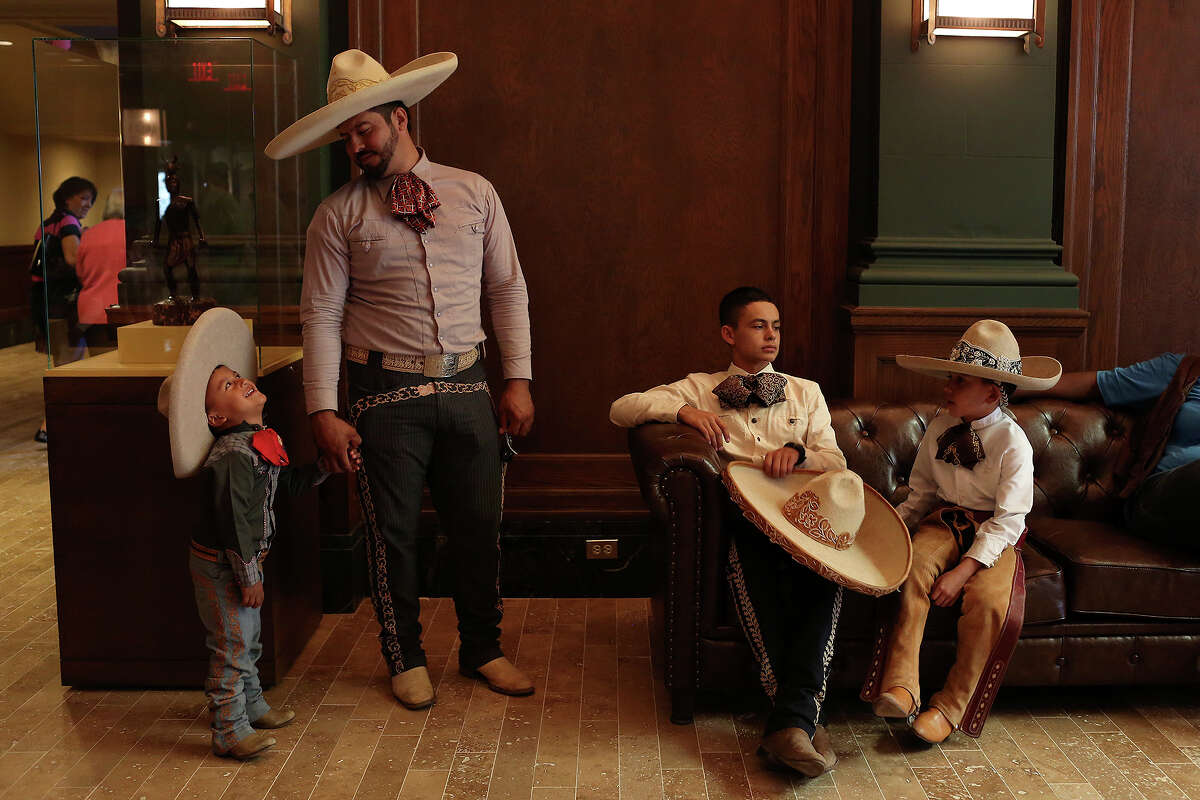Carlos Franco and his son, Carlos Franco, Jr., 3, wait with Edmundo Rios III, 17, Diego Rivera, 8, after performing with the San Antonio Charro Association during the grand opening celebration for the Briscoe Western Art Museum in San Antonio on Saturday, Oct. 26, 2013.