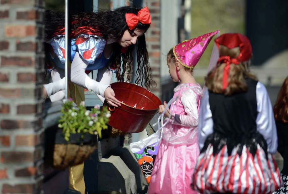 Beatrice Cruz, 18, of Seymour, dressed as Snow White, gives out candy to Ryann Walsh, 6, of Watertown, while working at Heavenlee Sent, a gift boutique, Saturday, Oct. 26, 2013 during the 7th annual downtown Seymour Trick or Treat Day. Photo: Autumn Driscoll / Connecticut Post