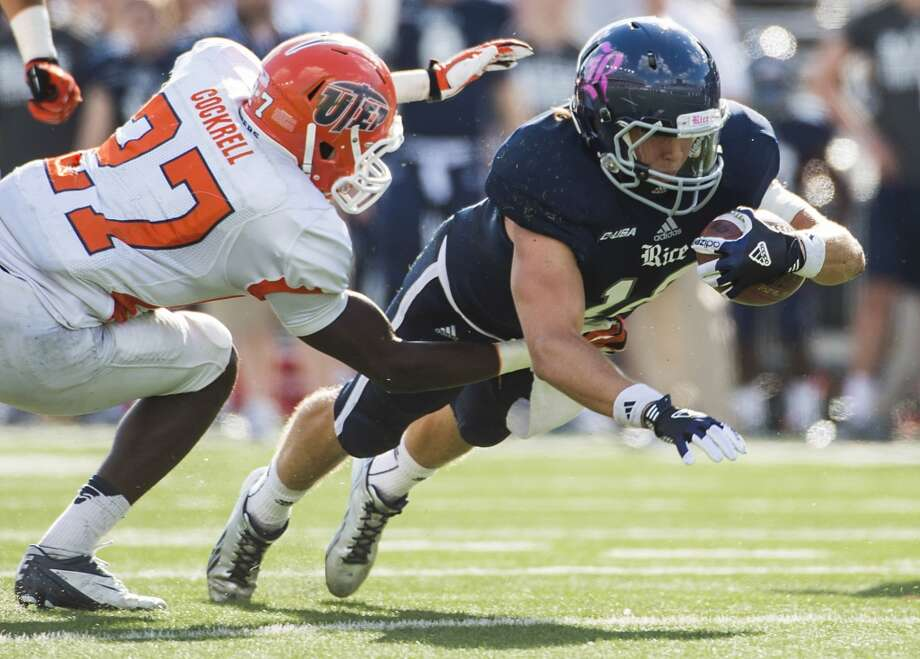 Rice quarterback Taylor McHargue dives for extra yardage past UTEP defensive back Devin Cockrell. Photo: Smiley N. Pool, Houston Chronicle