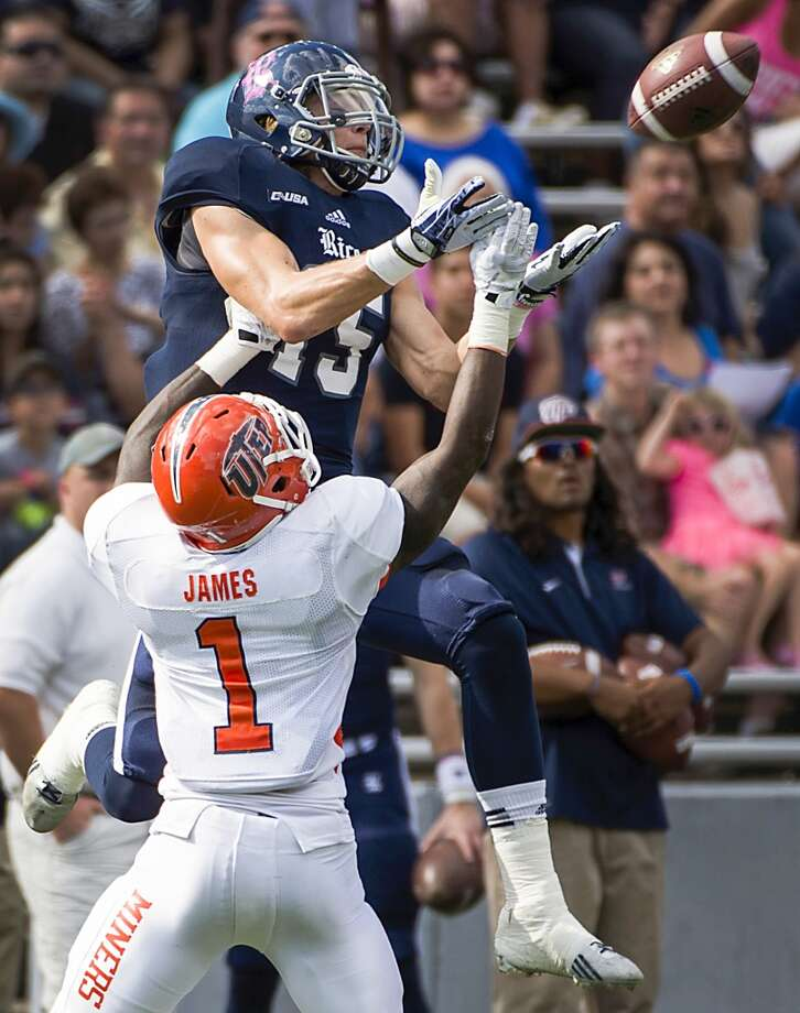 Rice wide receiver Jordan Taylor leaps over UTEP defensive back Adrian James for a pass. Photo: Smiley N. Pool, Houston Chronicle