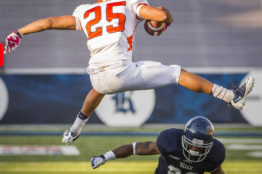 UTEP running back Nathan Jeffery leaps over Rice cornerback Anthony Canady. Photo: Smiley N. Pool, Houston Chronicle