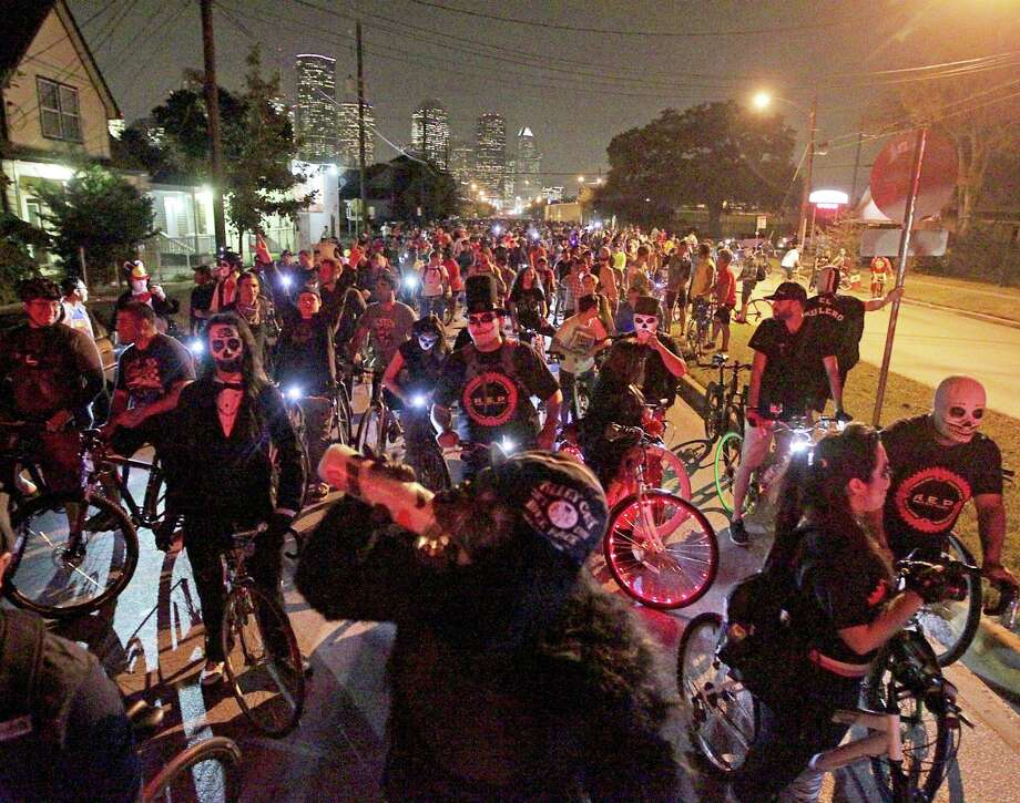 Thousands of bicyclist wait for a train at a railroad crossing on Houston Avenue during the Critical Mass bike ride Friday, Oct. 25, 2013, in Houston. The first to have a police escort.See video from the event at HoustonChronicle.com. Photo: James Nielsen, Houston Chronicle / © 2013  Houston Chronicle
