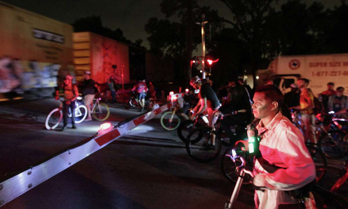 Thousands of bicyclist wait for a train at a railroad crossing on Houston Avenue during the Critical Mass bike ride Friday, Oct. 25, 2013, in Houston.
