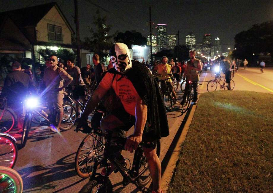 Thousands of bicyclist wait for a train at a railroad crossing on Houston Avenue during the Critical Mass bike ride Friday, Oct. 25, 2013, in Houston. Photo: James Nielsen, Houston Chronicle / © 2013  Houston Chronicle