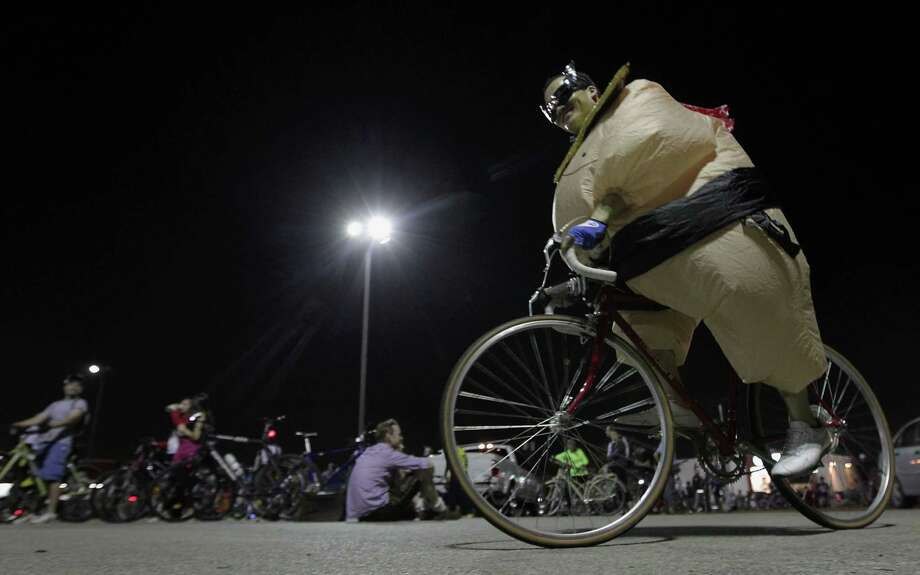 Lawrence Moore wears a sumo wrestler halloween costume during the Critical Mass bike ride Friday, Oct. 25, 2013, in Houston. Photo: James Nielsen, Houston Chronicle / © 2013  Houston Chronicle