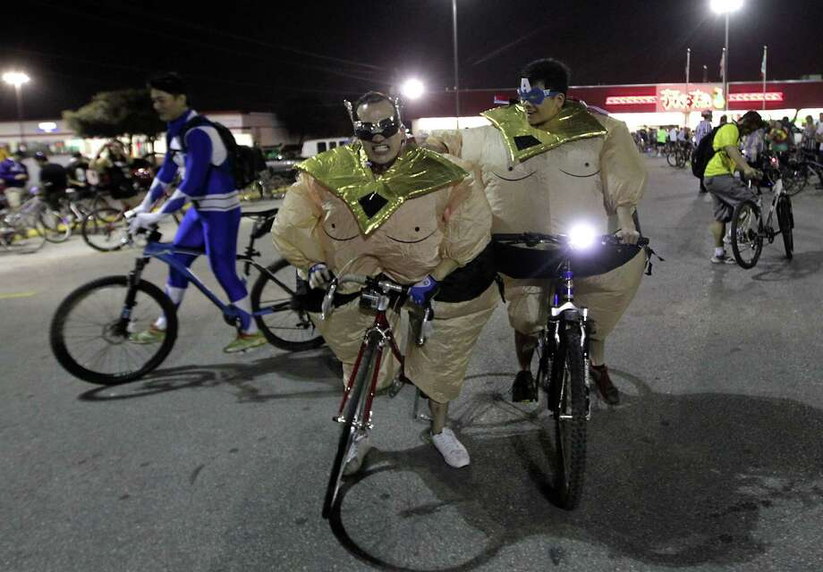 Lawrence Moore, 2nd from left, and Tam Nguyen wear sumo wrestler halloween costume during the Critical Mass bike ride Friday, Oct. 25, 2013, in Houston. Photo: James Nielsen, Houston Chronicle / © 2013  Houston Chronicle